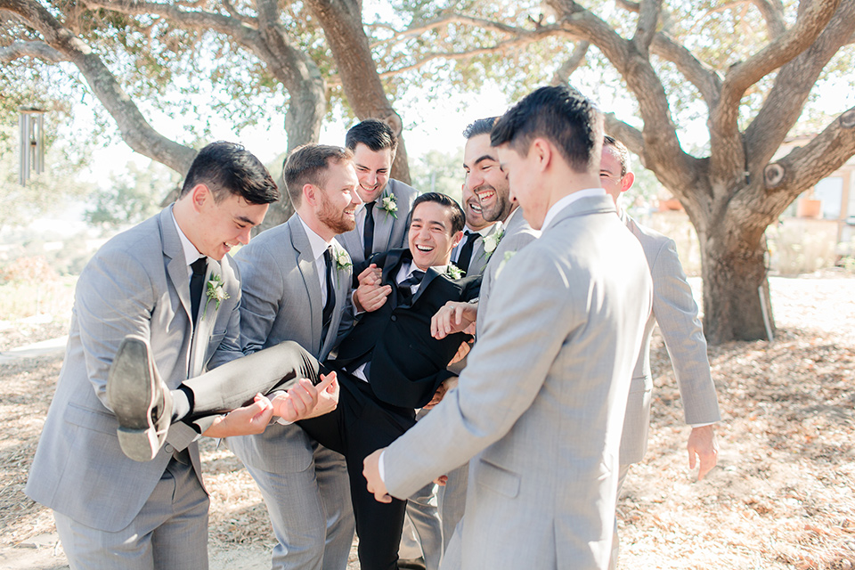 Arroyo-Grande-Wedding-groom-being-held-up-by-groomsmen-the-groom-wore-a-traditional-black-tuxedo-and-black-long-tie-while-the-groomsmen-wore-light-grey-suits-with-black-ties