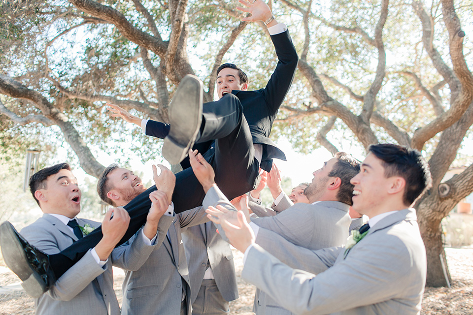 Arroyo-Grande-Wedding-groom-being-thrown-by-groomsmen-the-groom-wore-a-traditional-black-tuxedo-and-black-long-tie-while-the-groomsmen-wore-light-grey-suits-with-black-ties
