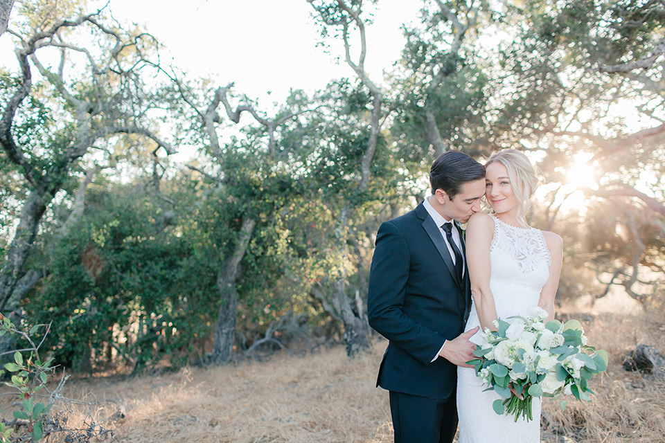 Arroyo-Grande-Wedding-groom-kissing-brides-shoulder-bride-in-a-boho-style-gown-with-a-keyhole-back-and-high-neckline-and-fringe-white-the-groom-wore-a-traditional-black-tuxedo-and-black-long-tie