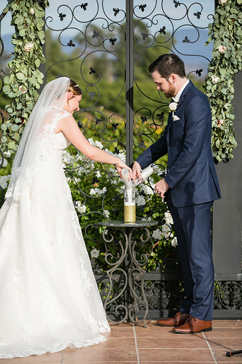 bride and groom pouring champagne at wedding venue in front of green vines and white florals