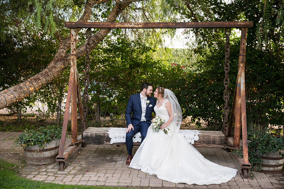Villa de Amore wedding bride and groom on a swing with bride wearing a tulle ballgown with lace details and straps and the groom wearing a dark blue suit