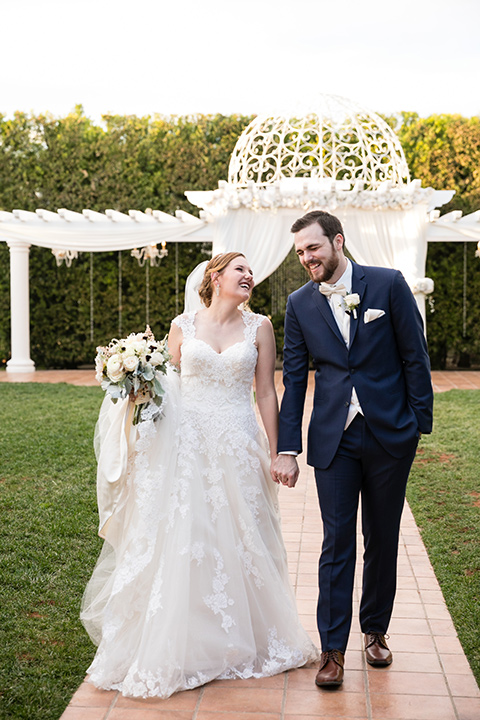 wedding bride and groom walking along brick path while holding hands