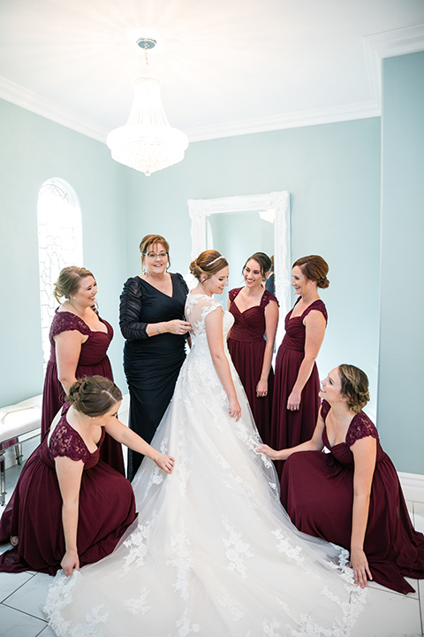 bridesmaids in burgundy dresses pose with bride in white gown