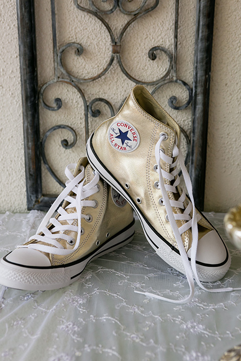 White converse shoes set up on white lace cloth to match wedding style