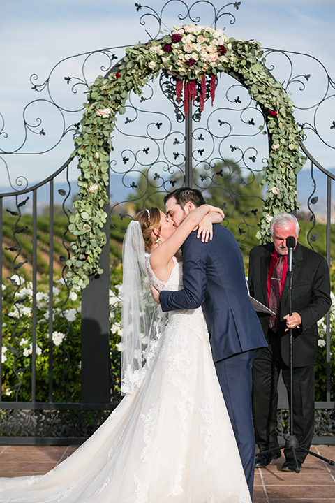 bride and groom share first kiss in front of altar at temecula vineyard wedding