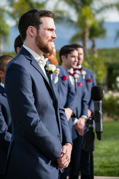 Villa de Amore wedding groom at the ceremony wearing a blue suit and a white bow tie