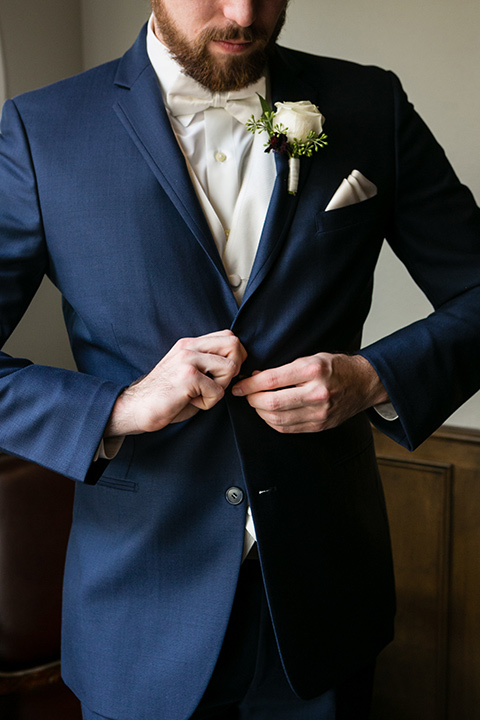 groom buttons button on blue suit with white bow tie, white pocket square, and white floral