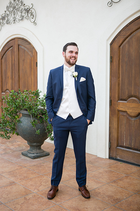 villa de amore wedding groom stands in front of venue with hands in pocket wearing a blue suit