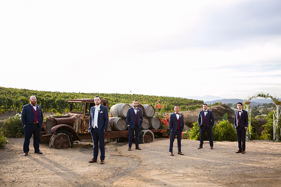 Groomsmen pose at temecula vineyard in front of rolling hills and vines