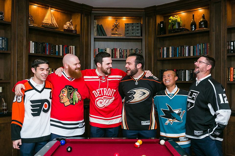 groom and groomsmen pose in front of pool table with arms around each other and wearing hockey jerseys