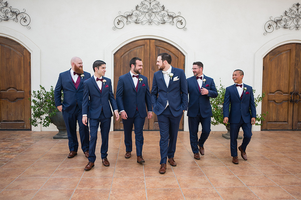 groom walks with the groomsmen in a blue suit with a white vest while groomsmen wear burgundy vests