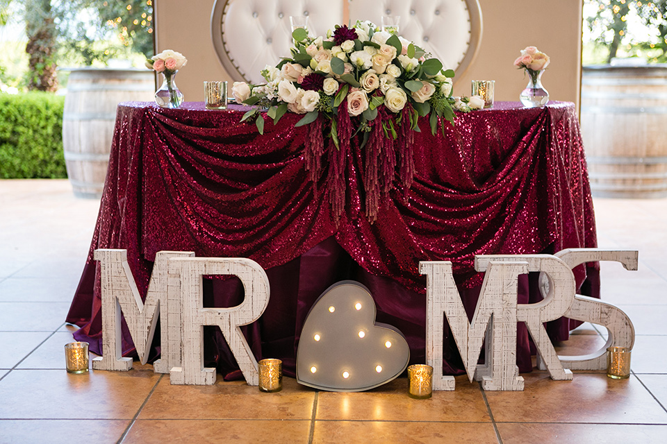 sweetheart table with letter blocks that say mr and mrs and a burgundy table cloth