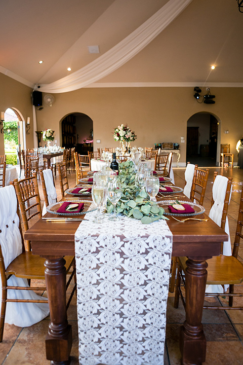 wedding tabe set up and decorations with white lace tablecloth and wooden chairs