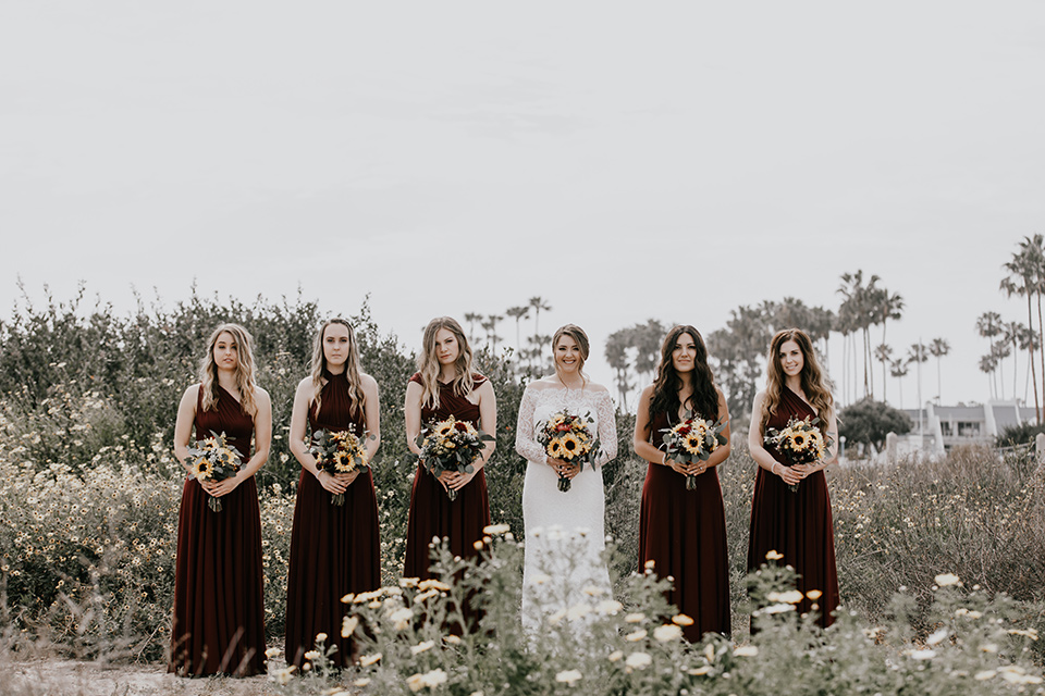 coronado-yacht-club-wedding-bride-and-bridesmaids-bridesmaids-in-red-dresses-bride-in-a-lace-form-fitting-gown