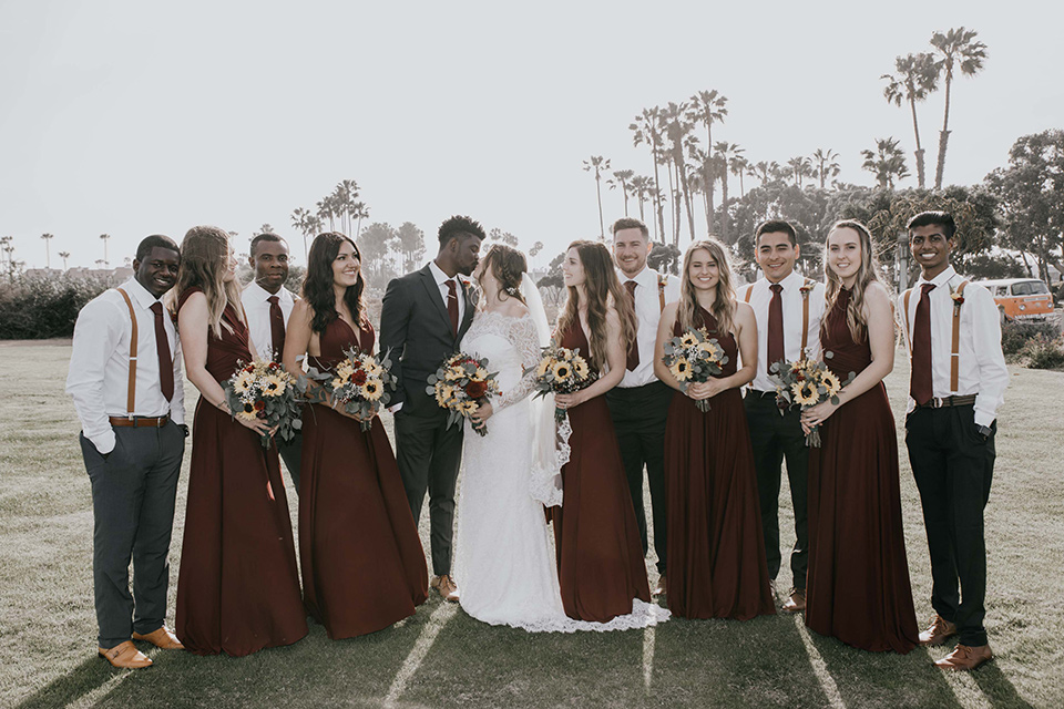 coronado-yacht-club-wedding-bride-and-groom-kissing-with-bridal-party-all-around-them-bridesmaids-in-red-dresses-groomsmen-in-a-casual-look-with-just-grey-pants-white-shirts-and-red-long-ties-bride-in-a-lace-form-fitting-gown-groom-in-a-charcoal-grey-suit-with-red-tie