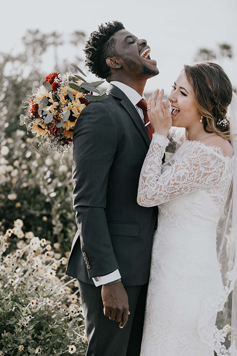 coronado-yacht-club-wedding-bride-and-groom-laughing-bride-in-a-lace-gown-with-sleeves-and-off-the-shoulder-detailing-groom-in-a-charcoal-grey-suit-and-deep-red-long-tie