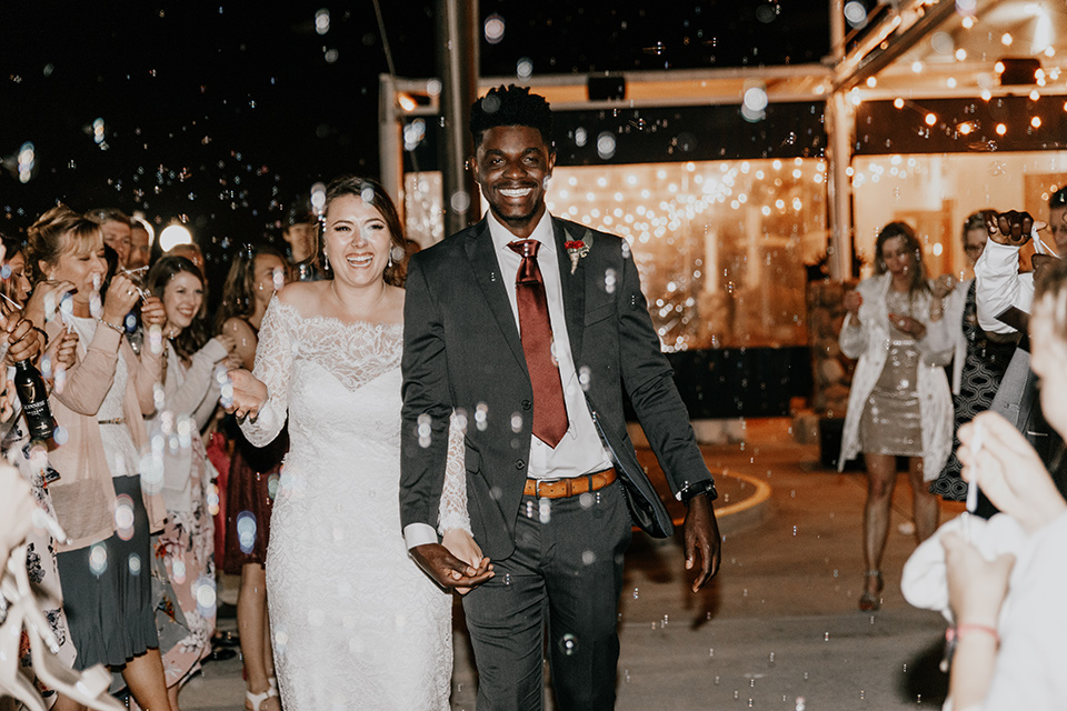 coronado-yacht-club-wedding-bride-and-groom-leaving-weddings-bride-in-a-lace-form-fitting-gown-with-sleeves-groom-in-a-charcoal-grey-suit-with-red-tie