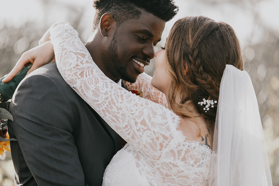 coronado-yacht-club-wedding-bride-and-groom-looking-at-eachother-bride-in-a-lace-form-fitting-gown-with-sleeves-groom-in-a-charcoal-grey-suit-with-red-tie