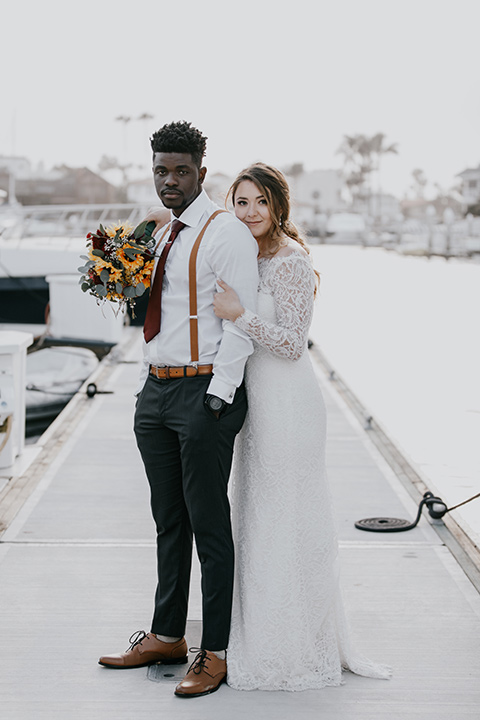 coronado-yacht-club-wedding-bride-and-groom-standing-at-the-marina-bride-in-a-lace-gown-with-sleeves-and-off-the-shoulder-detailing-groom-in-a-charcoal-grey-suit-and-deep-red-long-tie