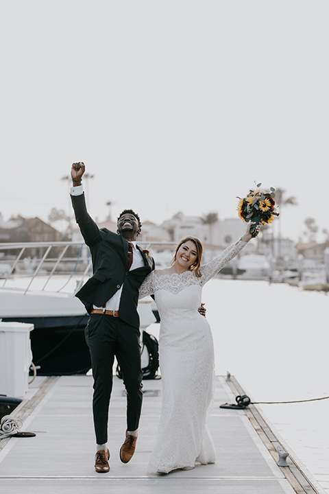 coronado-yacht-club-wedding-bride-and-groom-with-fists-in-the-air-bride-in-a-lace-dress-with-sleeves-and-groom-in-a-charcoal-suit-with-a-red-tie