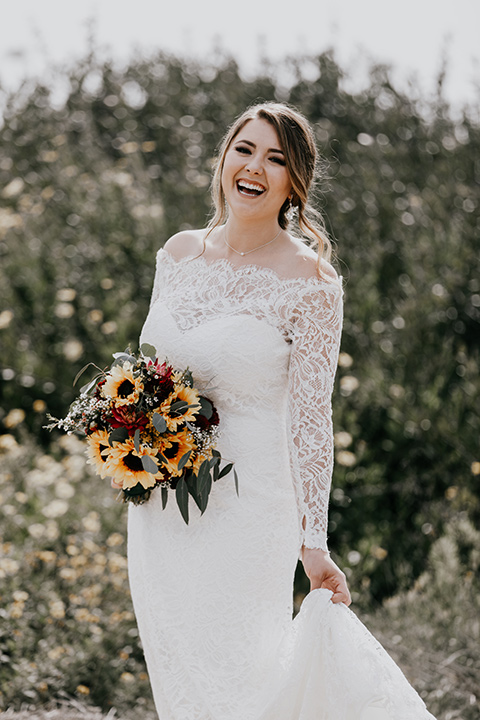 coronado-yacht-club-wedding-bride-laughing-alone-bride-in-a-lace-gown-with-sleeves-and-off-the-shoulder-detailing