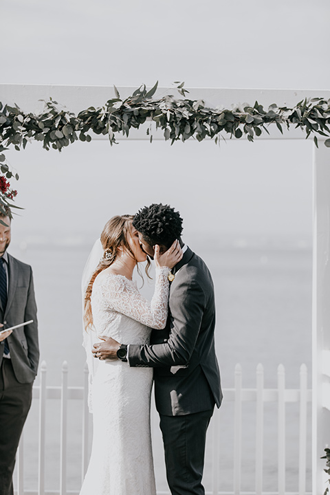 coronado-yacht-club-wedding-ceremony-kisss-bride-in-a-lace-dress-with-sleeves-and-groom-in-a-charcoal-suit-with-a-red-tie