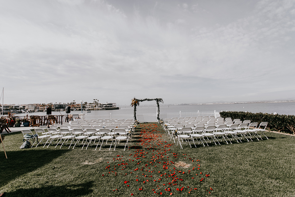 coronado-yacht-club-wedding-ceremony-space-with-white-chairs-and-wooden-archway
