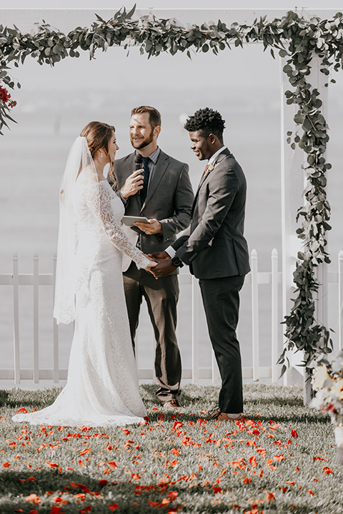 coronado-yacht-club-wedding-ceremony-bride-in-a-lace-gown-with-sleeves-and-off-the-shoulder-detailing-groom-in-a-charcoal-grey-suit-and-deep-red-long-tie