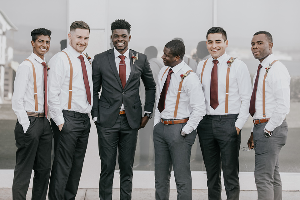 coronado-yacht-club-wedding-groom-and-groomsmen-groomsmen-in-a-casual-look-with-just-charcoal-pants-white-shirt-and-red-tie-groom-in-charcoal-suit-with-red-tie