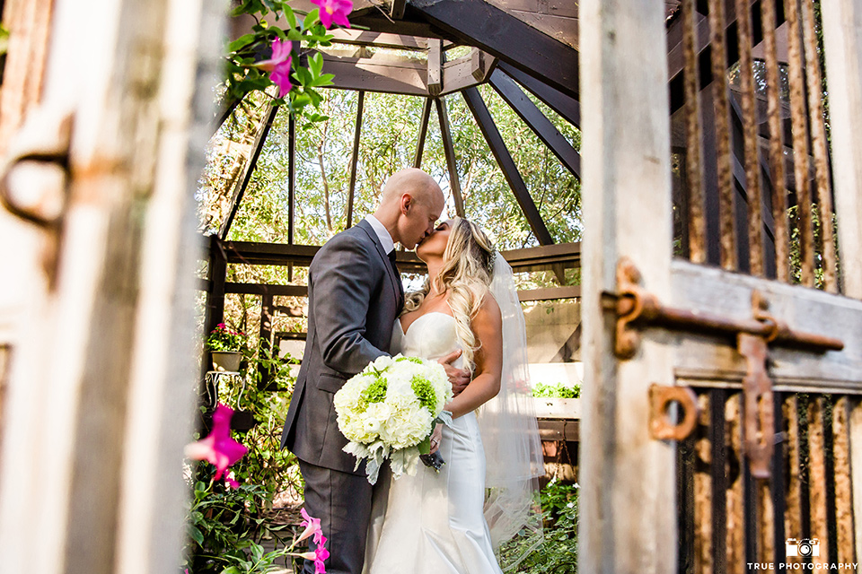 twin-oaks-weddings-bride-and-groom-in-gazebo-bride-in-a-strapless-fit-and-flare-gown-with-a-sweetheart-neckline-groom-in-a-charcoal-grey-suit-with-black-long-tie