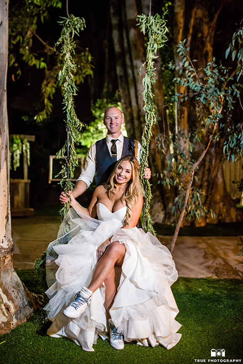 twin-oaks-weddings-bride-and-groom-on-swing-bride-in-a-strapless-fit-and-flare-gown-with-a-sweetheart-neckline-groom-in-a-charcoal-grey-suit-with-a-black-long