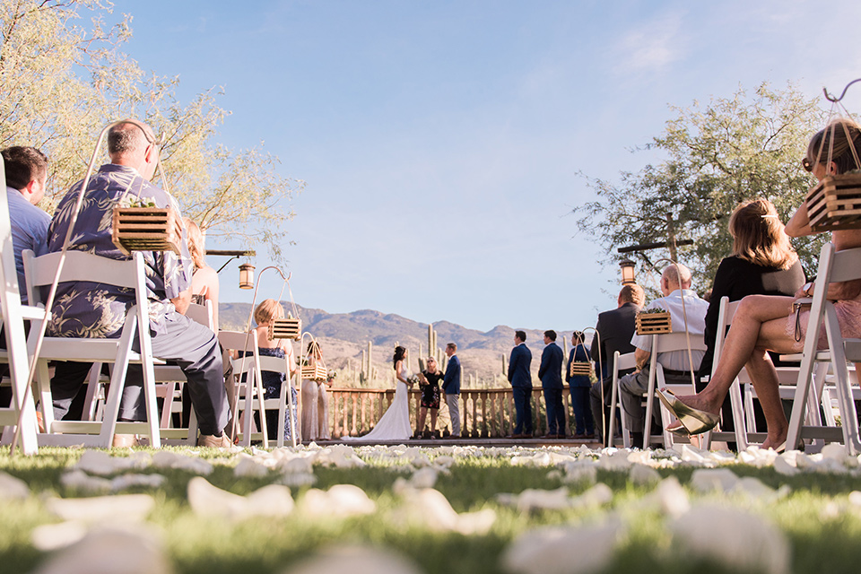 tanque-verde-ranch-arizona-wedding-ceremony-low-angle-bridesmaids-in-blush-toned-dresses-and-groomsmen-in-dark-blue-suits-the-bride-in-a-white-formfitting-gown-with-thin-straps-and-the-groom-and-in-grey-suit-pants-and-a-blue-suit-coat