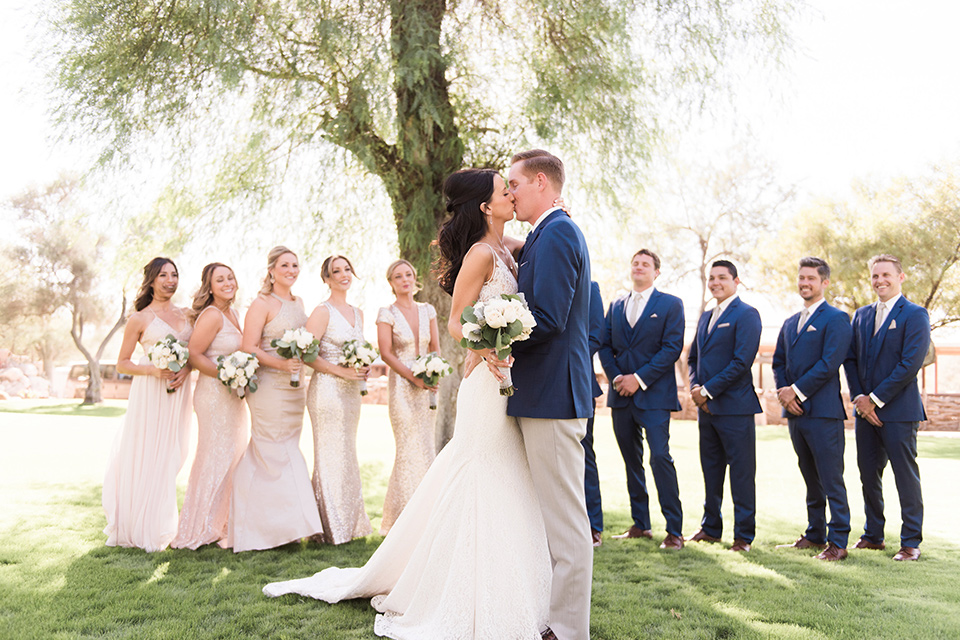 tanque-verde-ranch-arizona-wedding-brialparty-bridesmaids-in-blush-toned-dresses-and-groomsmen-in-dark-blue-suits-the-bride-in-a-white-formfitting-gown-with-thin-straps-and-the-groom-and-in-grey-suit-pants-and-a-blue-suit-coat