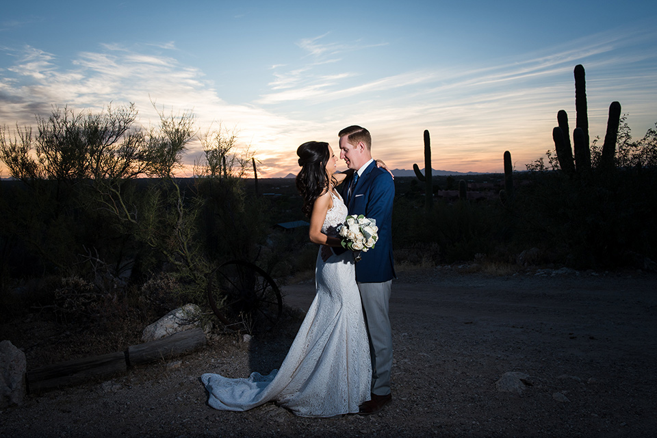 tanque-verde-ranch-arizona-wedding-bride-and-groom-at-sunset-the-bride-in-a-white-formfitting-gown-with-thin-straps-and-the-groom-and-in-grey-suit-pants-and-a-blue-suit-coat
