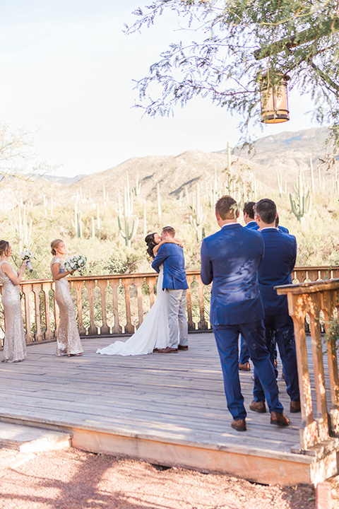 tanque-verde-ranch-arizona-wedding-bride-and-groom-first-kiss-the-bride-in-a-white-formfitting-gown-with-thin-straps-and-the-groom-in-grey-pants-and-a-blue-suit-coat