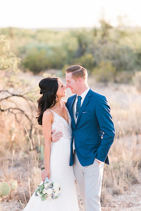 tanque-verde-ranch-arizona-wedding-bride-and-groom-looking-out-at-desert-the-bride-in-a-white-formfitting-gown-with-thin-straps-and-the-groom-in-grey-suit-pants-and-a-navy-blue-suit-coat