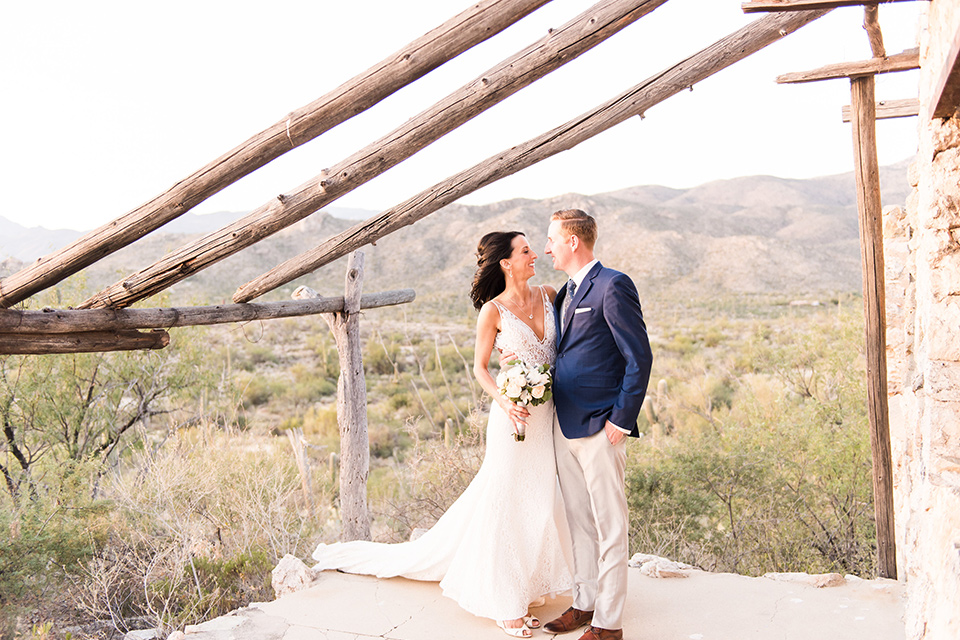 tanque-verde-ranch-arizona-wedding-bride-and-groom-ouside-venue-the-bride-in-a-white-formfitting-gown-with-thin-straps-and-the-groom-and-in-grey-suit-pants-and-a-blue-suit-coat