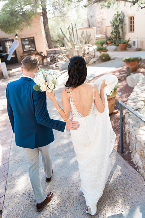 tanque-verde-ranch-arizona-wedding-bride-and-groom-walking-away-bride-in-a-white-formfitting-gown-with-thin-straps-and-the-groom-in-grey-pants-and-a-blue-suit-coat