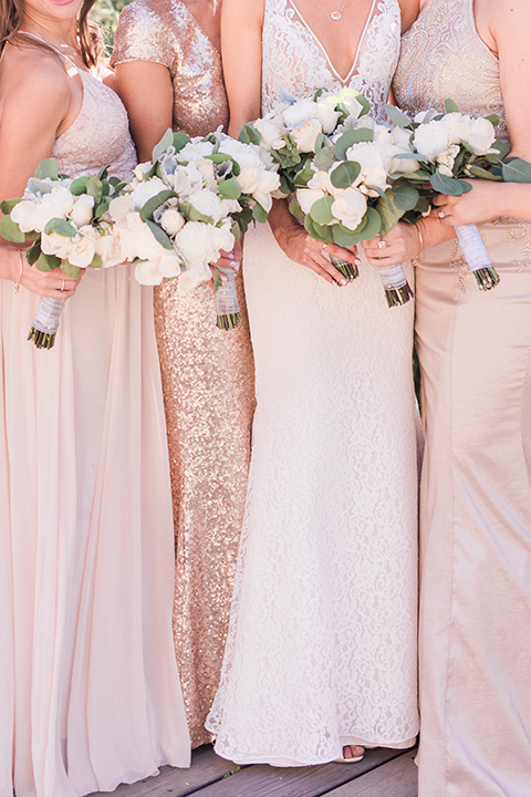 tanque-verde-ranch-arizona-wedding-close-up-on-bridesmaids-the-bride-in-a-white-formfitting-gown-with-thin-straps-the-bridesmaids-in-blush-toned-gowns