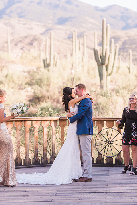 tanque-verde-ranch-arizona-wedding-first-kiss-the-bride-in-a-white-formfitting-gown-with-thin-straps-and-the-groom-in-grey-suit-pants-and-a-navy-blue-suit-coat