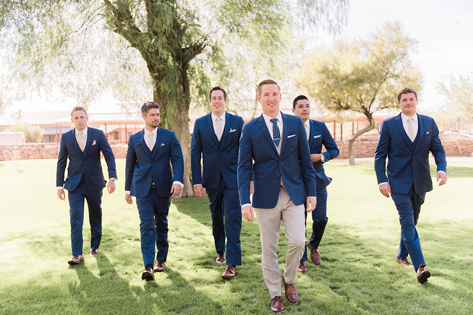 tanque-verde-ranch-arizona-wedding-groom-and-groomsmen-walking-groomsmen-in-dark-blue-suits-the-groom-and-in-grey-suit-pants-and-a-blue-suit-coat