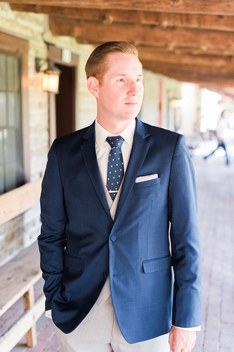 tanque-verde-ranch-arizona-wedding-groom-looking-to-the-side-in-grey-suit-pants-and-a-navy-blue-suit-coat