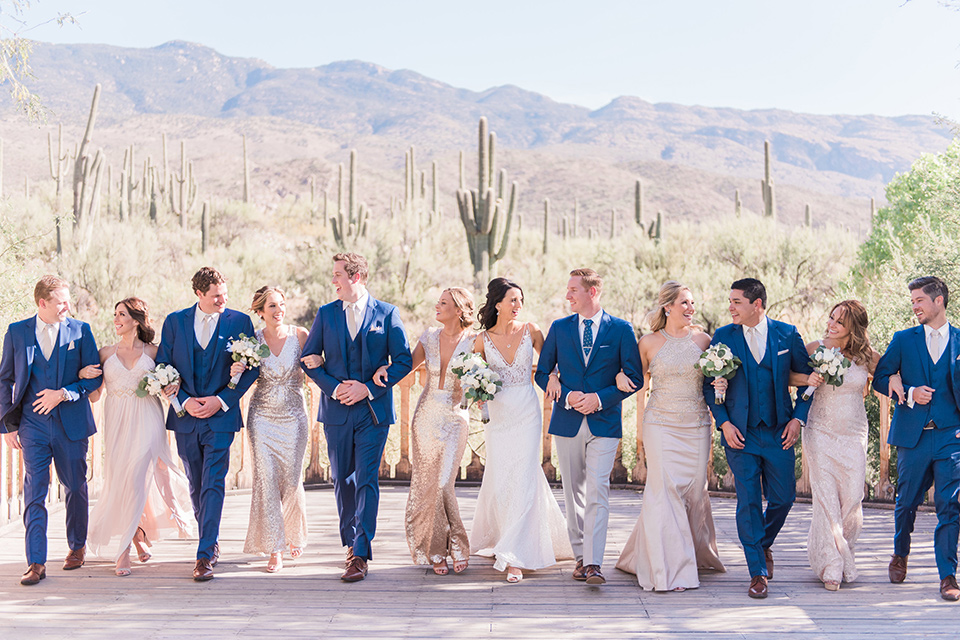 tanque-verde-ranch-arizona-wedding-groomsmen-and-bridesmaids-walking-with-couple-bridesmaids-in-blush-toned-dresses-and-groomsmen-in-dark-blue-suits-the-bride-in-a-white-formfitting-gown-with-thin-straps-and-the-groom-and-in-grey-suit-pants-and-a-blue-suit-coat