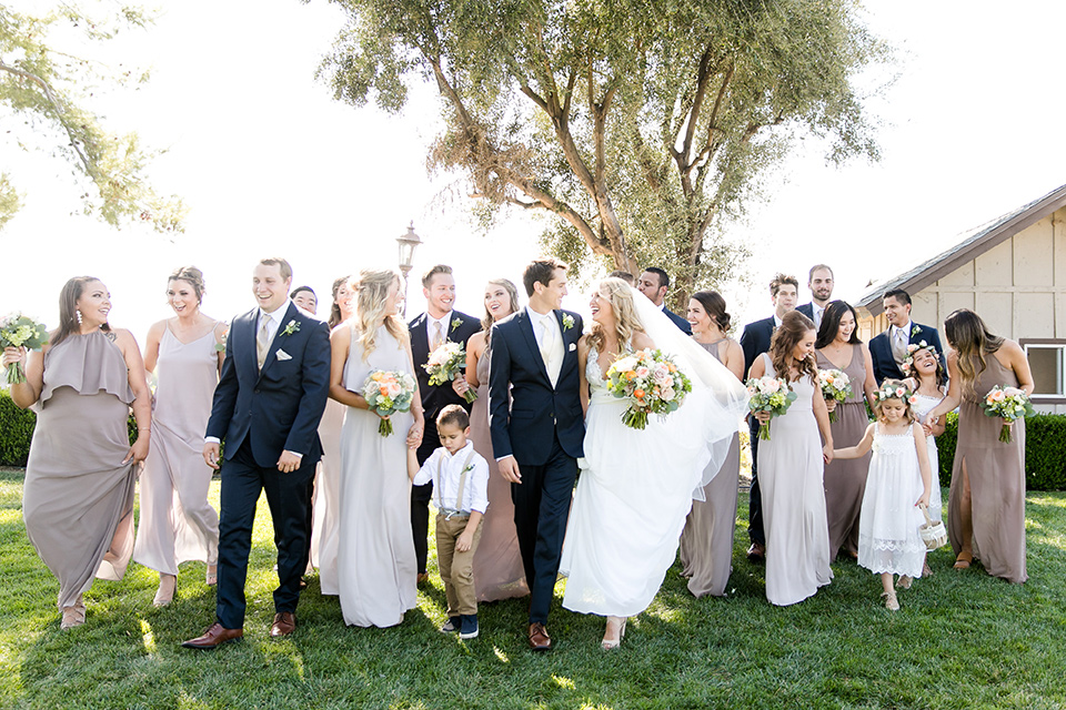 callaway-winery-wedding-bridal-party-walking-towards-camera-bride-in-a-flowing-white-gown-with-straps-and-a-deep-v-neckline-groom-in-a-navy-blue-suit-bridesmaids-in-taupe-and-nude-gowns-the-groomsmen-in-navy-blue-suits