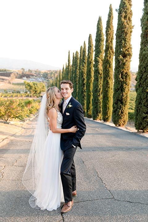 callaway-winery-wedding-bride-and-groom-by-tall-trees-bride-in-a-flowing-white-gown-with-a-deep-v-neckline-the-groom-in-a-navy-suit-and-white-tie