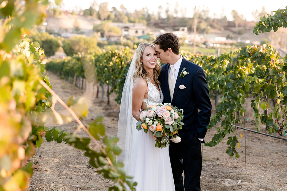callaway-winery-wedding-bride-and-groom-by-vines-bride-in-a-flowing-white-gown-with-straps-and-a-deep-v-neckline-groom-in-a-navy-blue