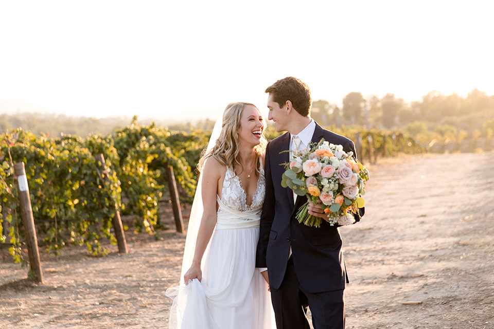 ccallaway-winery-wedding-bride-and-groom-walking-by-vines-bride-in-a-flowing-white-gown-with-straps-and-a-deep-v-neckline-groom-in-a-navy-blue