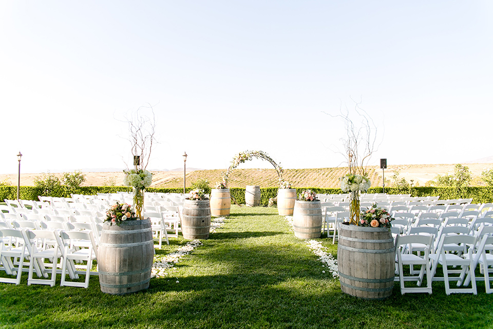 callaway-winery-wedding-ceremony-setup-with-white-chairs-and-a-floral-covered-arch