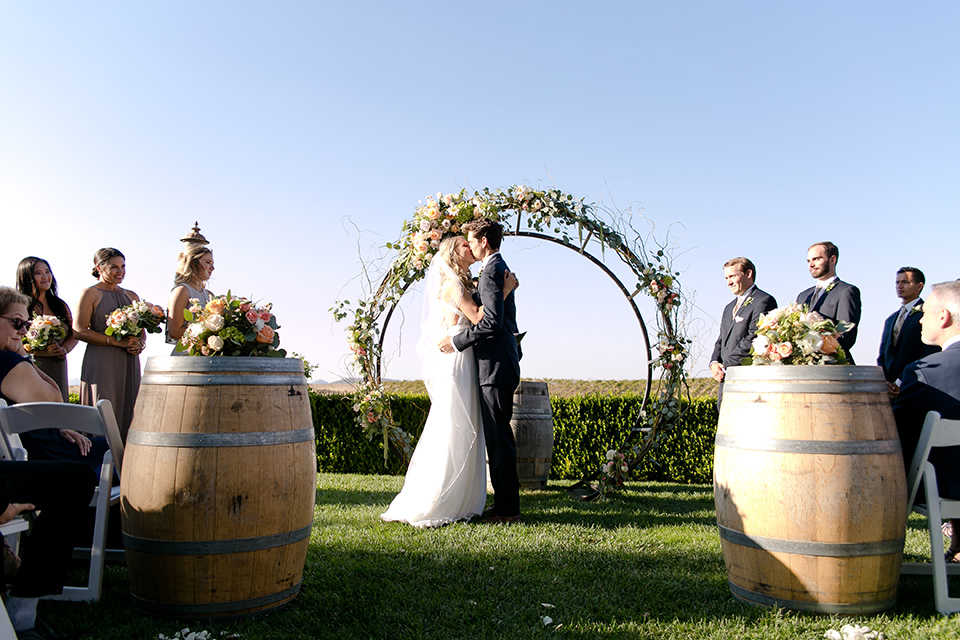 callaway-winery-wedding-first-kiss-the-bride-wearing-a-white-flowing-gown-with-a-deep-v-neckline-and-the-groom-in-a-navy-blue-suit
