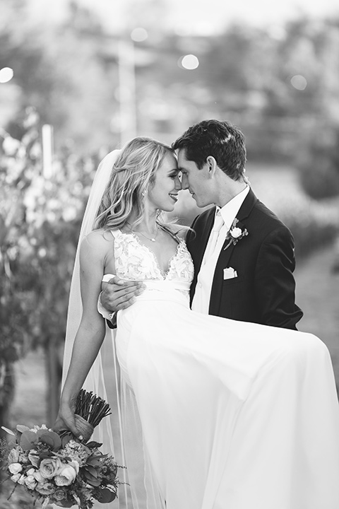 callaway-winery-wedding-groom-carrying-bride-the-bride-in-a-flowing-white-gown-with-straps-and-the-groom-in-a-navy-suit-with-a-white-tie